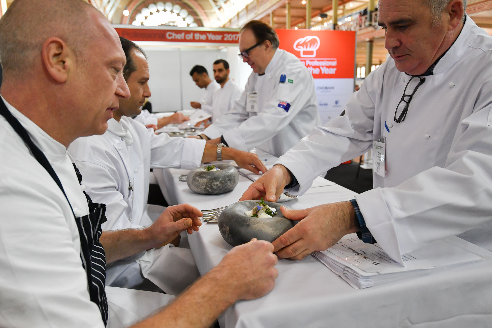 Melbourne, 30 May 2017 - Tom Milligan of the Bocuse d'Or Academy Australia delivers the fish dish for Donovan Cooke from The Atlantic Restaurant a judge of the fish plate to taste at the Australian selection trials of the Bocuse d'Or culinary competition held during the Food Service Australia show at the Royal Exhibition Building in Melbourne, Australia. Photo Sydney Low