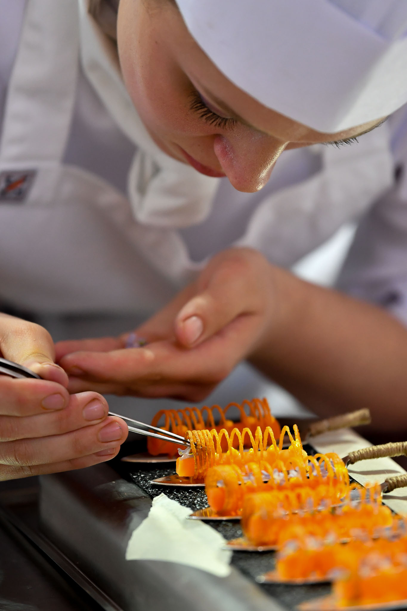 Melbourne, 30 May 2017 - Laura Skvor commis chef assisting Michael Cole of the Georgie Bass Café & Cookery in Flinders prepares a garnish for the meat platter at the Australian selection trials of the Bocuse d'Or culinary competition held during the Food Service Australia show at the Royal Exhibition Building in Melbourne, Australia. Photo Sydney Low